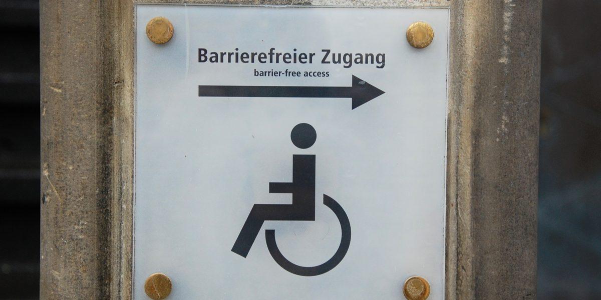 Zeigt ein Schild, dass auf einen barrierefreien Zugang verweist.